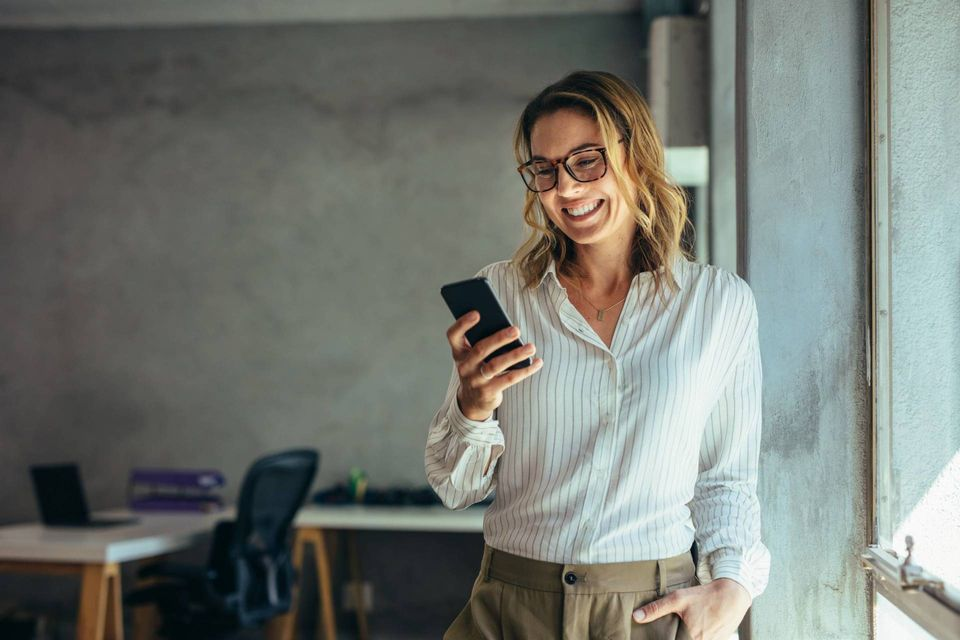 Real estate agent smiling at cell phone and typing for client